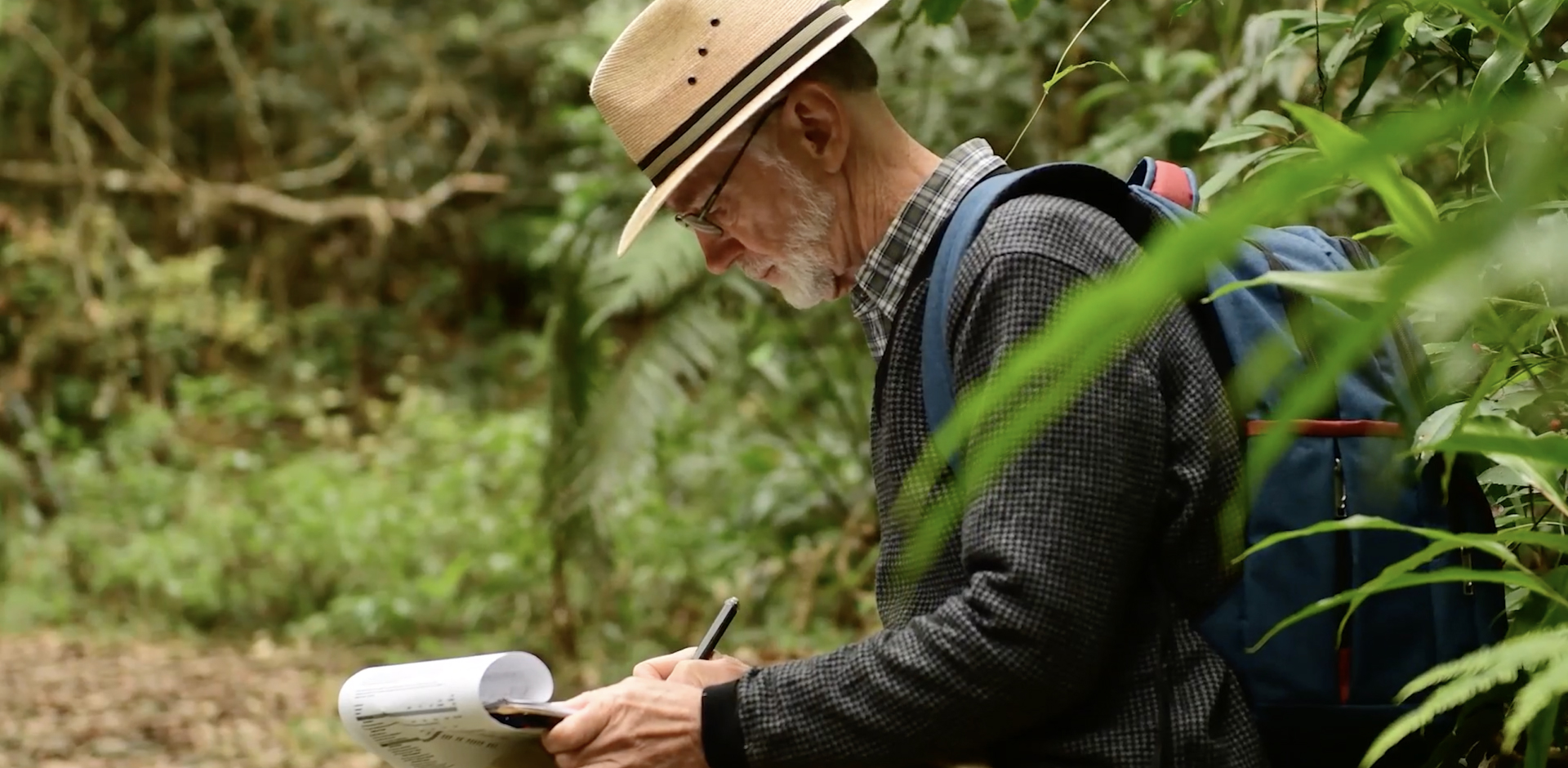 A second shot of Peter Chesson writing notes while conducting research in the jungle